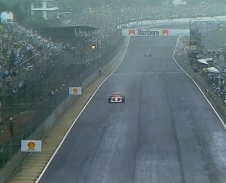 Senna recebe a bandeira quadriculada para vencer seu primeiro GP do Brasil com Patrese logo atrás