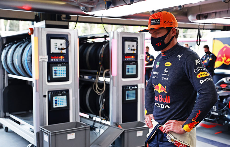 Verstappen com os pneus em cobertores de aquecimento ao fundo, no box da Red Bull